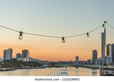 festoon lighting with sunset cityscape over river with pastel tones room for text or quotes