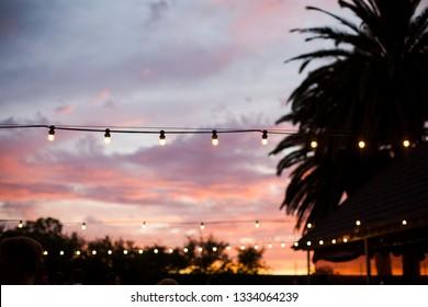 Festoon lights against pink and purple sunset