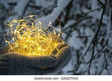 The festoon lights in hands outdoor.