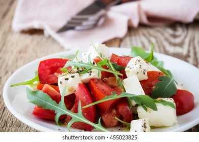 Feta arugula salad with tomatoes on white plate, summer vegetarian food concept