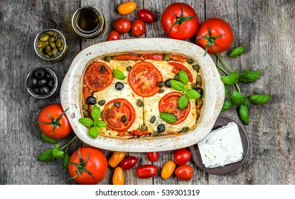 Feta baked with tomatoes. Greek food of mediterranean diet. Vegetarian dish for healthy eating.