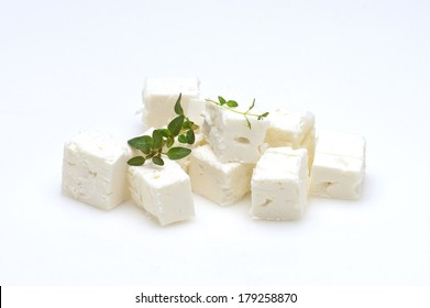 feta cheese cubes and oregano on a white background