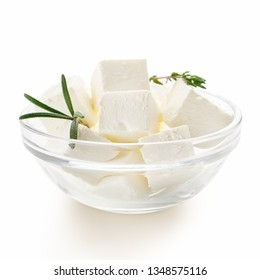Feta cheese cubes and rosemary in glass bowl on white background. Organic cheese concept