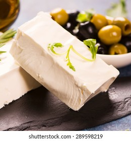 Feta cheese with fresh herbs, black and green olives, selective focus. Square image