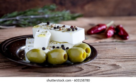 Feta cheese with green olives on a wooden background