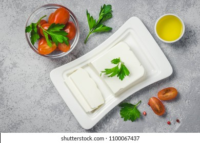 Feta cheese on plate with tomatoes, herbs, olive oil and spices. Top view, space for text.