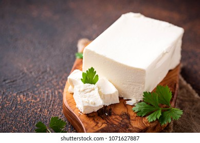 Feta cheese on rusty background. Selective focus