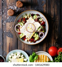 Feta cheese salad in ceramic bowl served with olives, tomatoes, onions, coriander, olive oil, halloumi cheese and basil over dark wooden background. Top view, flat lay. Square image