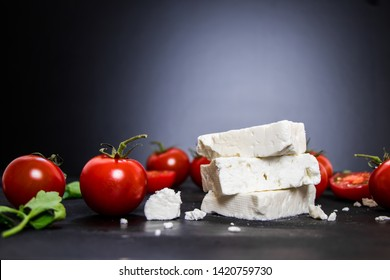 Feta cheese with tomatoes on black background
