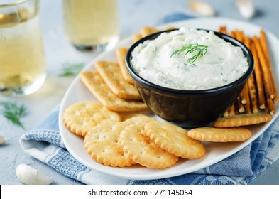 Feta cream cheese dill garlic dip with crackers. toning. selective focus