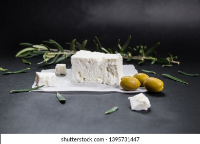 Feta Greek cheese with olives on black background