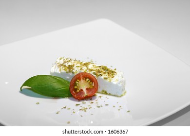 Feta, tomato, basil and olive on white porcelain