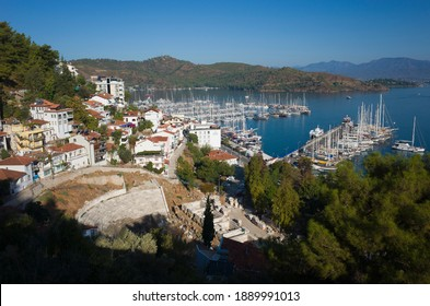 Fethiye, Turkey - 28 September, 2019: View of Fethiye harbour with turquoise water and mountains, Ruins of Ancient Theater Fethiye Antik Tiyatrosu on foreground
