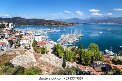 Fethiye, Turkey - March 28, 2021: View of Fethiye harbour with yachts and boats and mountains. There are ruins of Ancient Theater Antik Tiyatrosu on foreground. Mugla Province.