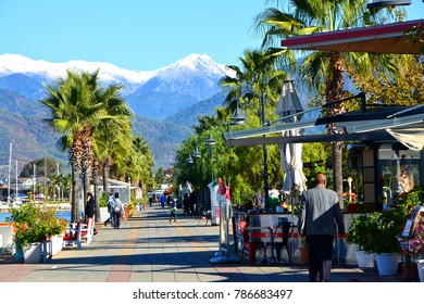 FETHIYE, TURKEY - November 22, 2017: Peoples on a sunny winter day on the waterfront on a background of snow-capped mountains
