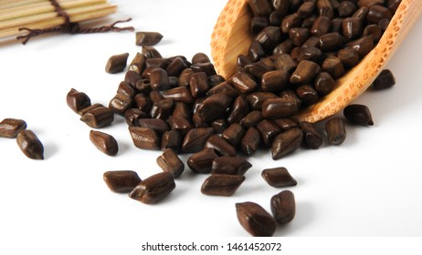 Fetid cassia seed also called ketsumei-shi on wooden spoons scattered isolated on a white background. Asia traditional Chinese medicine. Good for the eyes. .Cassia herb Tea.