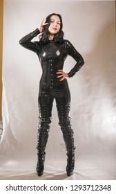 fetish bdsm girl in black latex on white studio background