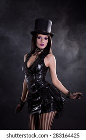 Fetish young woman in black dress and tophat, studio shoot on smoky background
