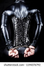 fetishist in shiny lycra catsuit with laced up pvc corset and hands in cuffs behind her back. capture from behind. hogtied.