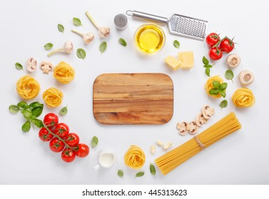 Fettuccine  and spaghetti with ingredients for cooking pasta on a white background with blank of wooden kitchen board, top view. Flat lay