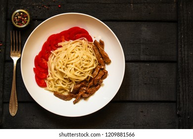 Fettuccine spaghetti pasta with tomatoes and herbs. Top view