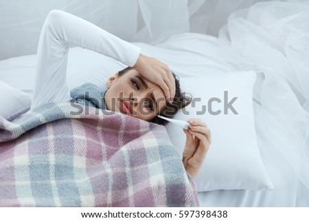 Fever And Cold. Portrait Of Beautiful Woman Caught Flu, Having Headache And High Temperature. Closeup Of Ill Girl Covered In Blanket, Feeling Sick Holding Thermometer. Health care. High Resolution