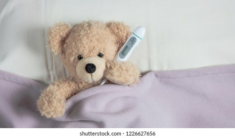 Fever, kids cold and flu, covid coronavirus concept. Cute teddy in bed, holding a thermometer