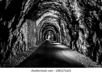 A few blurred, gostly human figures viewed from behind, inside an old, dark, scary tunnel surrounded by bare rocks, walking toward a bright light at the end