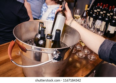 A few bottles of wine in an ice bucket. The bartender pulls out his hand a bottle of chilled wine from an ice bucket.