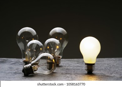 A few burned old bulbs and one light bulb on a gray concrete background. Top view.