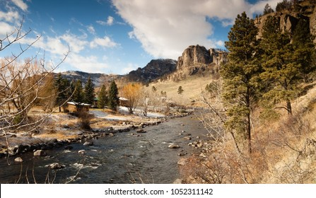 A few cabins line the waterfront of a wild scenic river below mountainous buttes in the Western USA