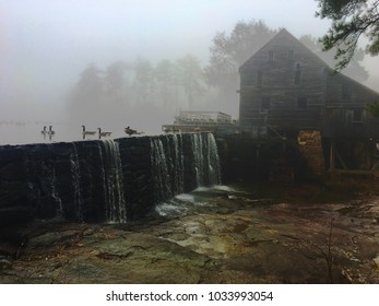 A few Canadian geese swim in the pond above the waterfall at the old gristmill at Historic Yates Mill Park in Raleigh North Carolina (Triangle Area) on a foggy winter morning.