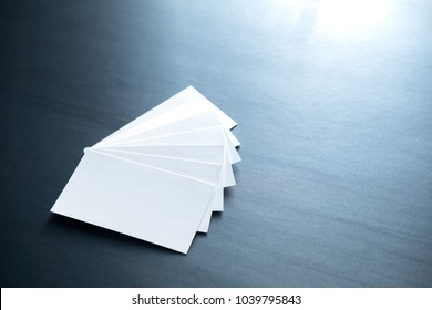 few clean white business cards with space for text on a black surface