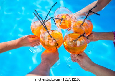 a few cocktails in hands of people on blue background. a circle of cocktails apprelated spritz in hands of people against background of blue water