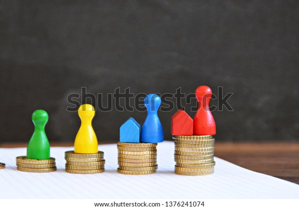A few coins are stacked in heaps on each other and together form an upward curve, on each pile is a figure in a different color, standing next to houses - concept for financing real estate
