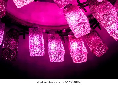 few crimson lamps of decorative modern shaped lamps on ceiling, crimson coral white lamps with light against dark background, many modern ceiling lamps with golden ornament, high quality resolution