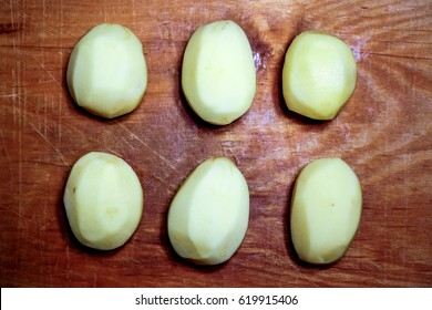 few cutting raw peeled potatoes against old wooden background. top view to potato circles. raw food background