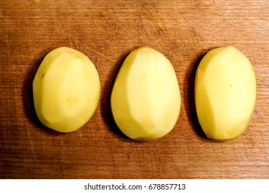 few cutting raw peeled potatos against old wooden background. top view to potato circles. raw food background