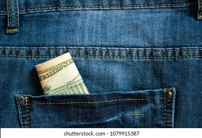 A few dollars stick out of my pocket. Paper money is in a ji-pocket. Cash bills are stored in a jeans pocket. Pocket money for small expenses.