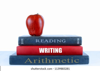 A few dusty books standing up on a light table with a white background. An apple sits on top of the books titled reading, writing and arithmetic. Education, learning and back to school concept