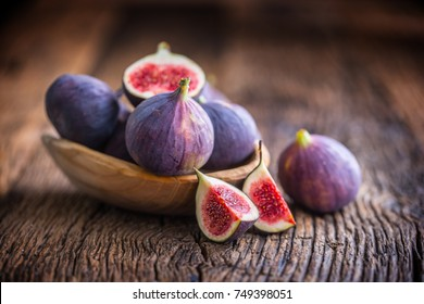 A few figs in a bowl on an old wooden background.