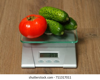 Few fresh cucumbers and tomato on the scales that show the weight in grams.