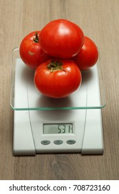 Few fresh tomatoes on the scales that show the weight in grams.