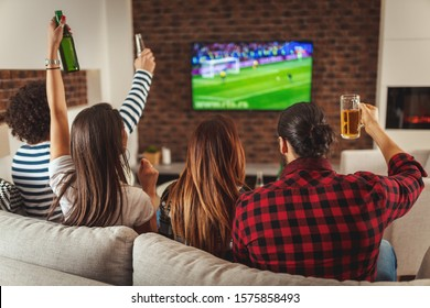 A few friends, fans of sports, love spending their free time at home together looking football game at TV. They are screaming and gesturing for a victory.