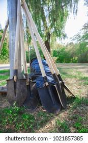 few garden shovels and black bag on  summer nature.