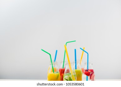 A few glass bottles with different fruit coctails and colored straws on a white background.