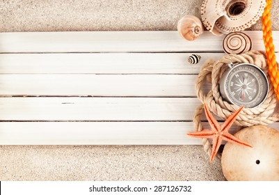 Few marine items on a wooden planks over sandy background.
