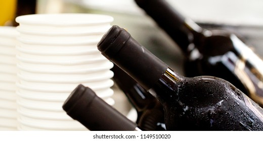 few misted bottles of chilled wine with drops of water and paper white cups prepared for a party or a holiday