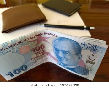 a few one hundred turkish lira banknotes on the table