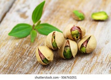 Few open pistachio nuts in nutshell on rustic wooden surface